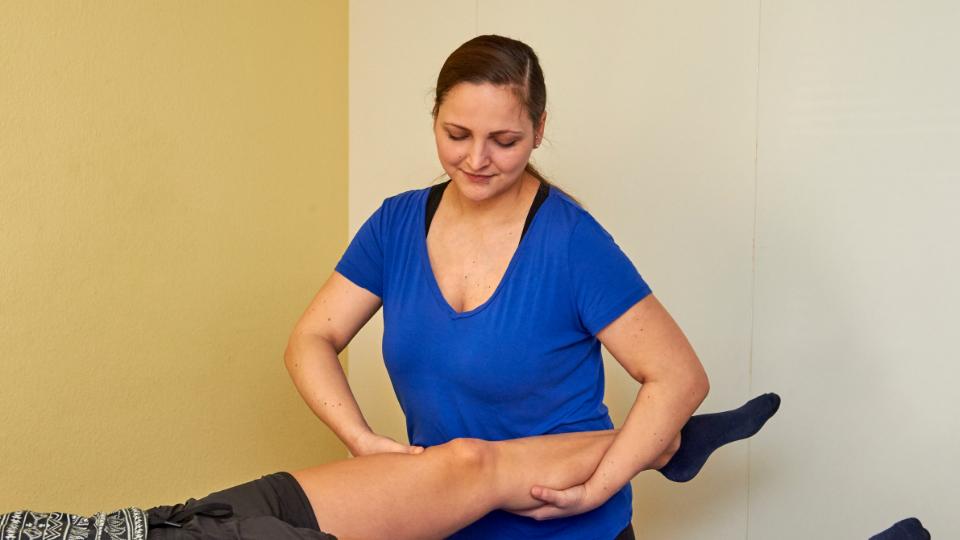 Mitarbeiterin bei der physiotherapeutischen Behandlung